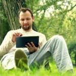 stock-footage-young-happy-man-with-tablet-computer-by-the-tree-in-park-dolly-shot