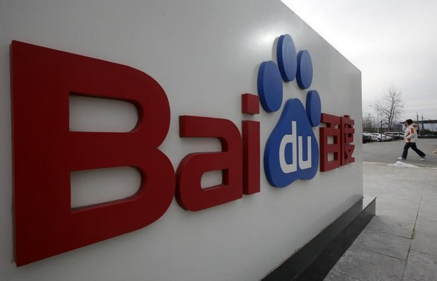 A woman walks past the company logo of Baidu at its headquarters in Beijing
