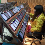 Worker-sits-in-front-of-a-bank-of-Apple-iPhone-5c-units-downloading-installing-and-uninstalling-apps-in-a-cycle
